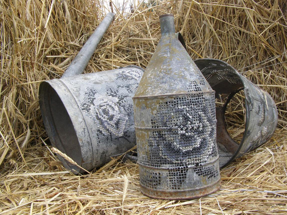 """Severija Inčirauskaitė-Kriaunevičienė. """"Tarp miesto ir kaimo"""". 2008. Metalinis kibiras, laistytuvas, bidonas, medvilniniai siūlai.  Siuvinėjimas kryželiu, gręžimas"""