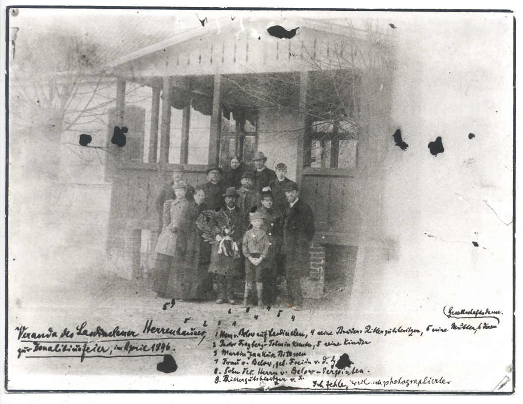 """F. Tecnerio užrašas: """"Lazdynėlių savininkų namo veranda Donelaičio šventei, 1896 m. balandžio mėn. [8 d. – D. K.] 1. Lazdynėlių savininkas fon Belovas, 4. jo broliai, dvarininkai, 5. jo motina, 6. jos bičiulė, 2. Tolminkiemio kunigas Fraibergas, 5. jo vaikai, 3. Martynas Jankus iš Bitėnų, 7. ponia fon Belov, gimusi fon G(?), 8. Belovų iš Serpentų sūnus (Serpentai buvo 4,7 km nuo Gumbinės – D. K.), 9. Dvaro savininkas X. Manęs nėra, nes aš fotografuoju."""" Nuotrauka iš D. Kauno rinkinių"""