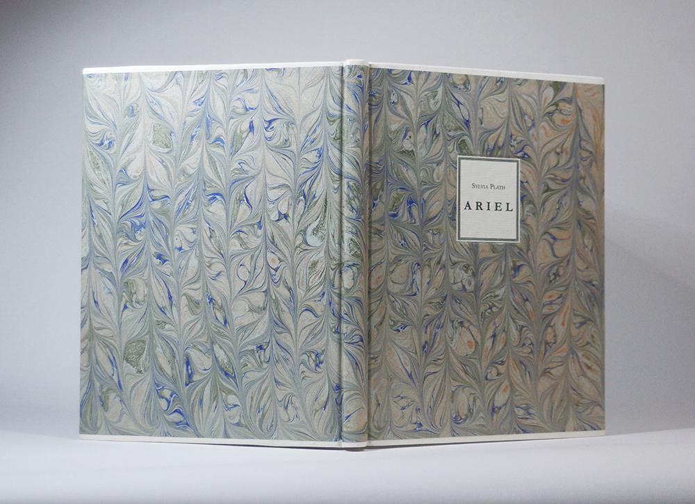 """Sylvia Plath """"Ariel"""" (Faber & Faber, 1968). Specialiai maketuotas leidinys.  Millimeter binding, arba Danish Rubow, stiliaus įrišimas. Baltos, alūnu išdirbtos ožkos odos juostelės, rankų darbo marmurinis popierius, popierinė lipdė; 16,5 x 22 x 1,3 cm."""