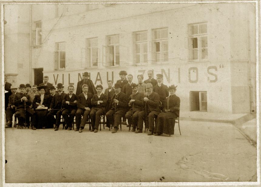 """""""Vilniaus žinių"""" redakcija ir administracija 1905 metais: Sėdi iš kairės: Aleksandras Ratkus (spaustuvės sargas); Antanas Rucevičius (bendradarbis); Jurgis Baltrušaitis (vertėjas; redakcijos pasiuntinys); Marija Piaseckaitė (Šlapelienė; """"Vilniaus žinių"""" knygyno vedėja); Augustinas Paškevičius (knygyno darbuotojas, ekspeditorius), Martynas Kukta (spaustuvės vedėjas), Adolfas Vėgėlė (vertėjas), Jonas Kaunas (vertėjas); Pranas Klimaitis (vertėjas); redakcijos pasiuntinys; Petras Vileišis (""""Vilniaus žinių"""" redaktorius ir leidėjas); Kazys Puida (sekretorius), Gabrielius Landsbergis-Žemkalnis (administratorius), Gabrielė Landsbergaitė (perrašinėtoja). Stovi iš kairės: spaustuvės darbuotojas; Mečislovas Dovoina-Silvestravičius (korespondentas); Kostas Stiklius (korektorius, spaustuvės darbuotojas); pasiuntinys; pasiuntinys; Jonas Siabas (buhalteris, knygyno darbuotojas); ekspeditorius. LMAVB."""