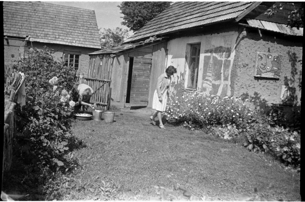 Augmėnai, Vinco Kisarausko tėviškė. Kairėje – mama Jadvyga, dešinėje – žmona Saulė, ant namo sienos – S. Kisarauskienės sieninė tapyba ir V. Kisarausko mozaika. 1967 m.