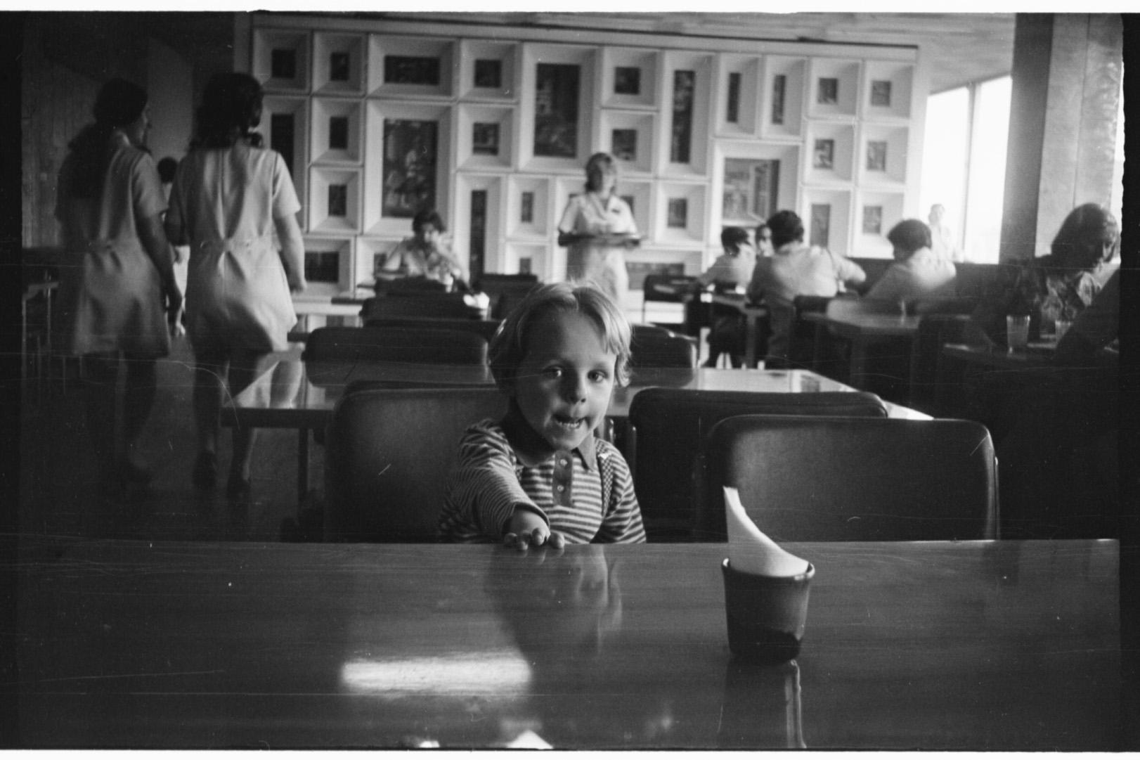 Sūnus Danielius Centrinės universalinės parduotuvės kavinėje. Fone – V. Kisarausko pano (dabar sunaikintas). 1974 m.