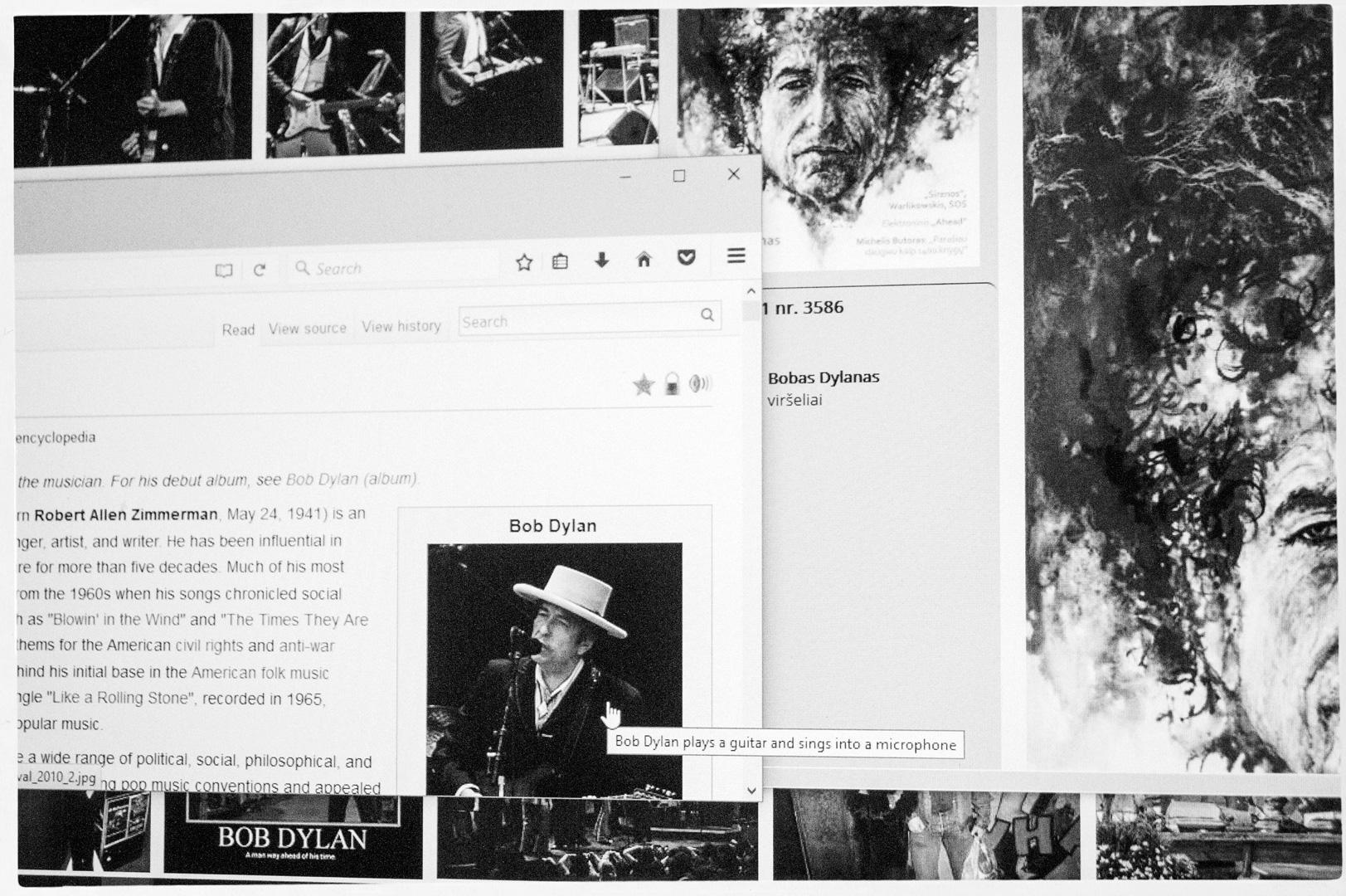 Bobas Dylanas groja gitara ir dainuoja į mikrofoną
