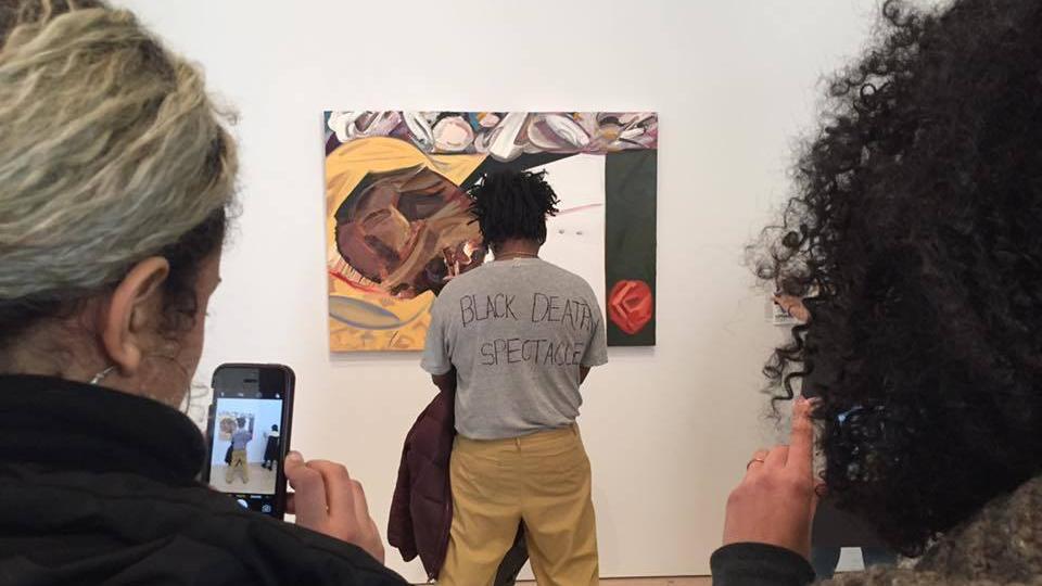 Protestuotojas stovi prieš D. Schutz paveikslą
